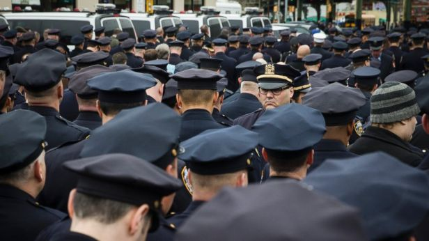 A lone police officer stands front as other colleagues turn their backs while Mayor Bill de Blasio speaks during the funeral of New York Police Department Officer Wenjian Liu at Aievoli Funeral Home, Sunday, Jan. 4, 2015, in the Brooklyn borough of New York.
